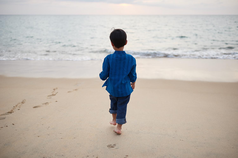 boy-walking-on-sandy-beach-in-thailand-family-session.jpg
