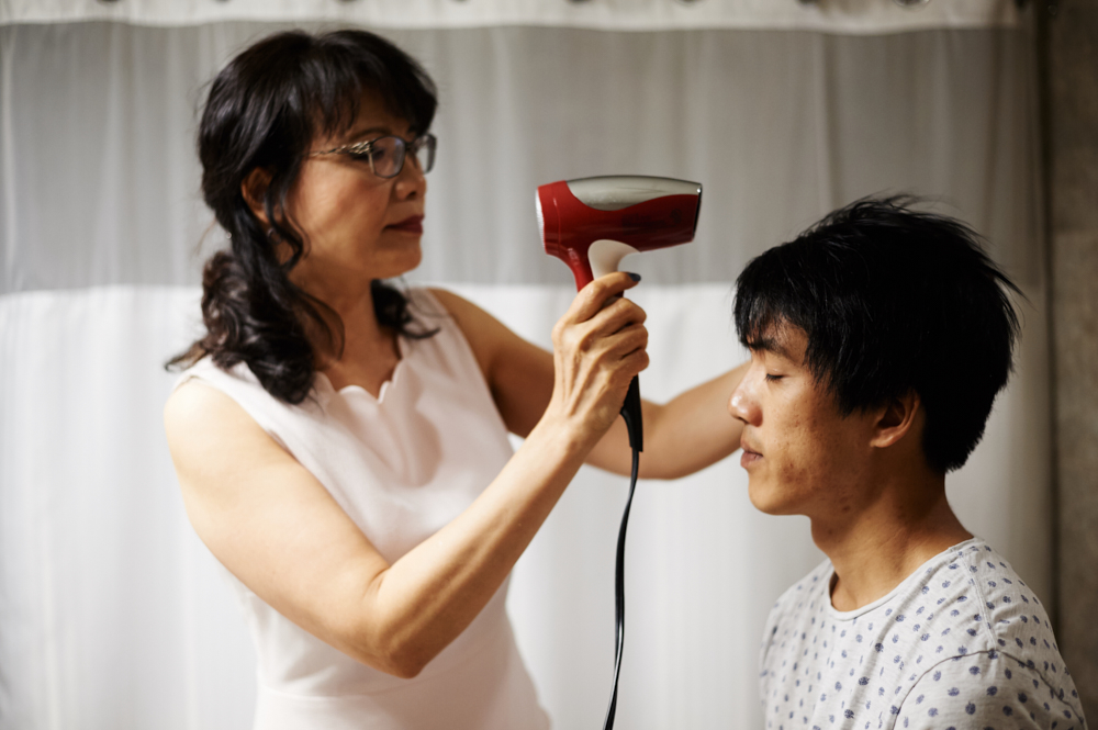 mother blow drying her sons hair