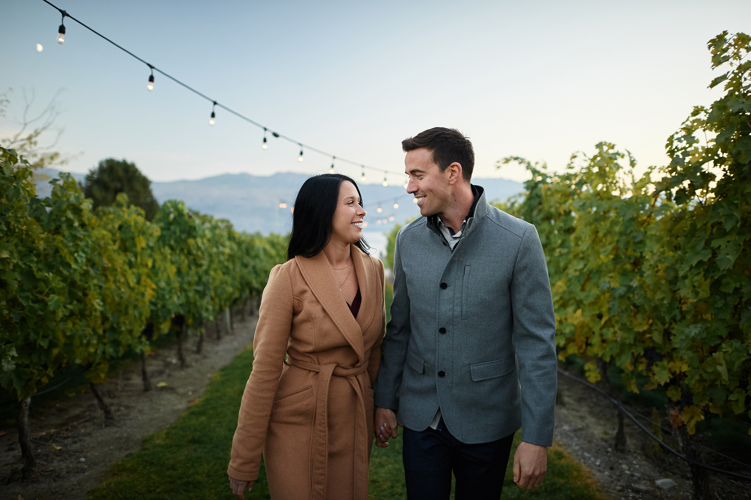 engaged couple walking in okanagan vineyard