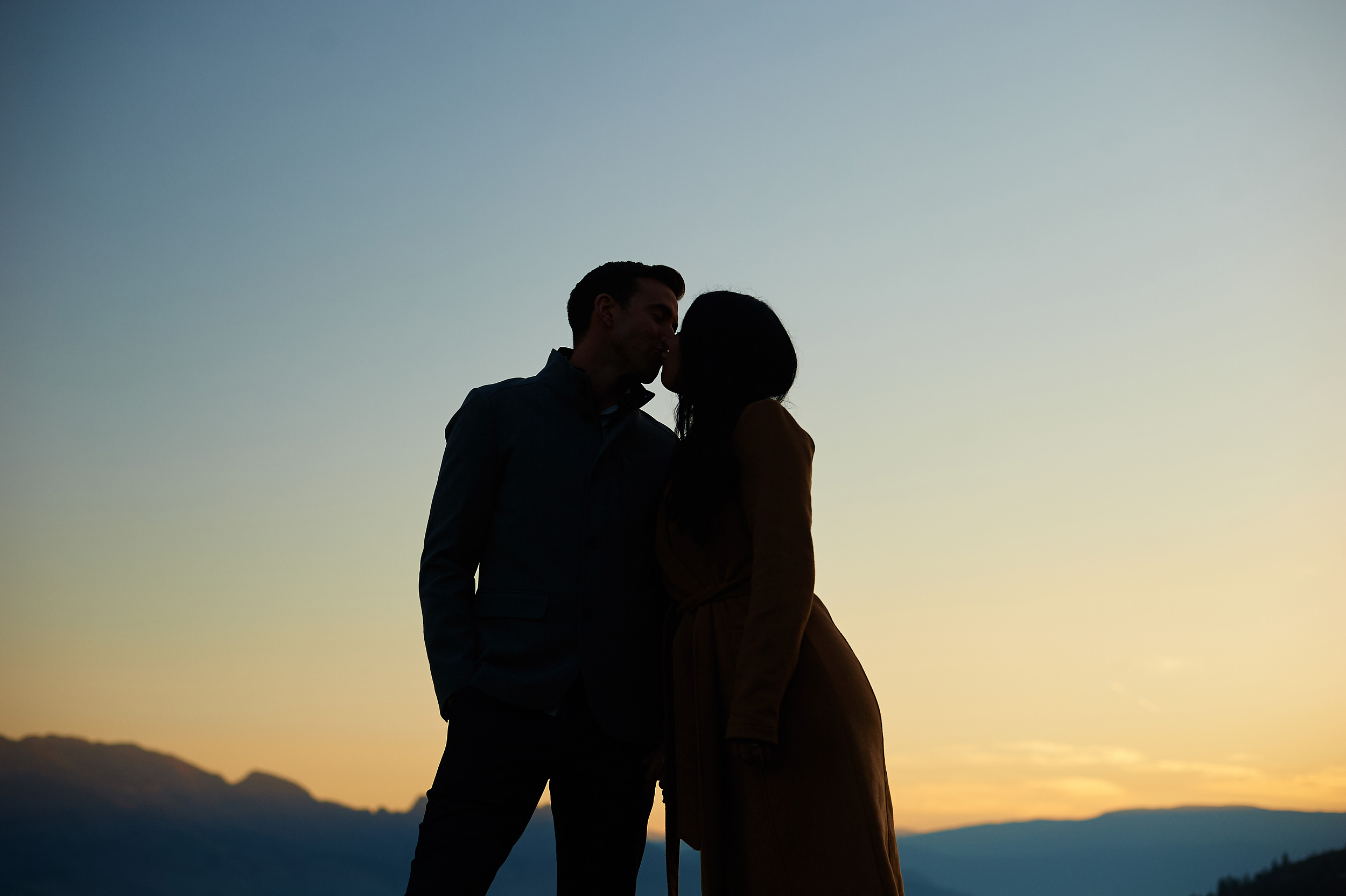 engaged couple in sunset over okanagan mountain