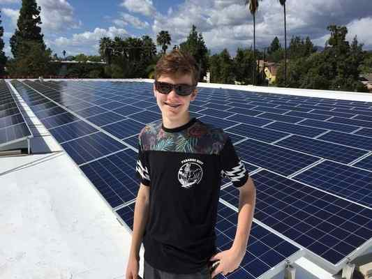 Brett Barnard has 744 solar panels on the roofs on his two Pasadena businesses - STORBOX Self Storage business and The Wine Grotto. It's the largest non-institutional photovoltaic solar array in the city. His 14-year-old son Cole is shown here in front of some of the panels.