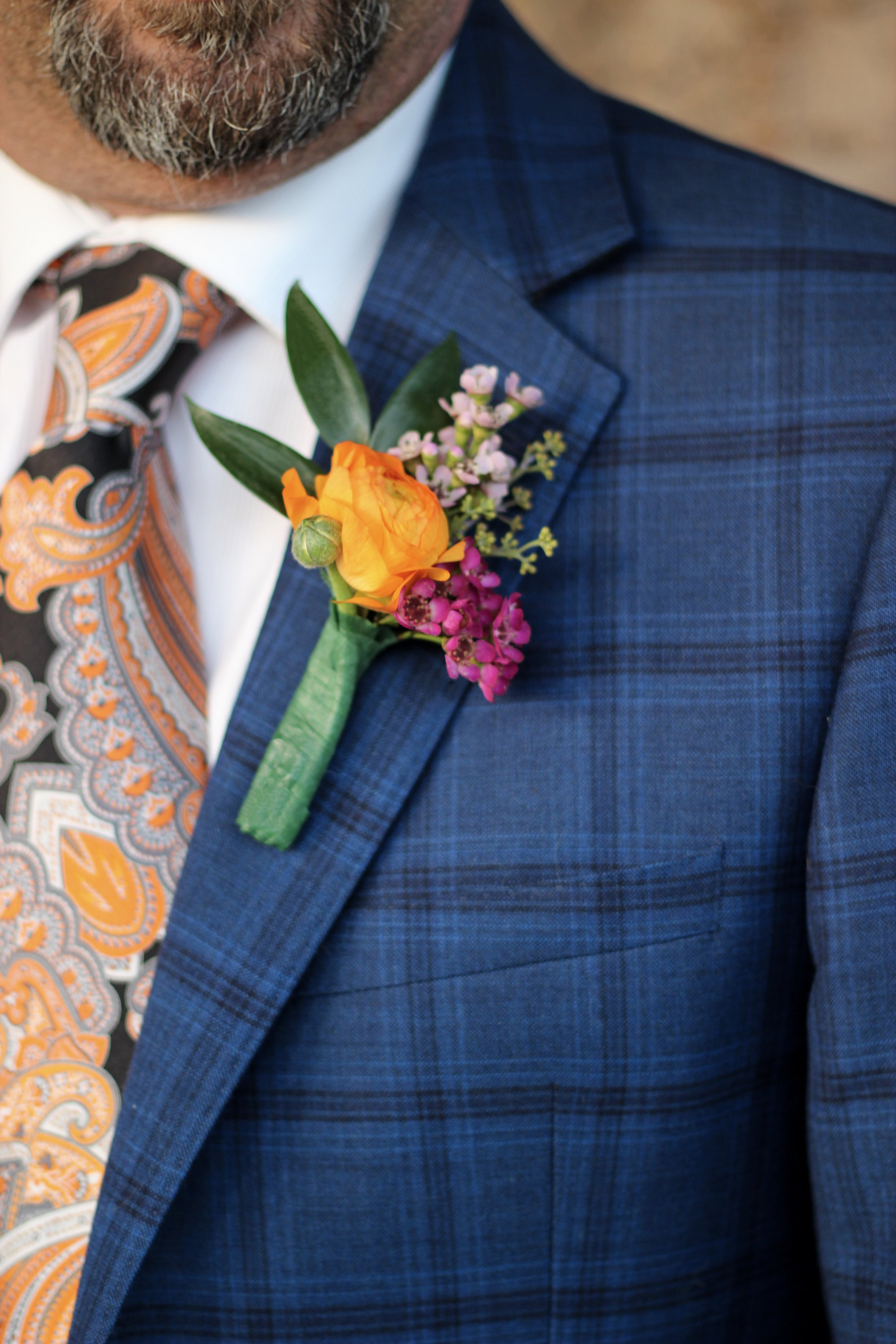 Orange ranunculus and purple wax flower boutonniere with seeded eucalyptus - Roots & Wildflowers