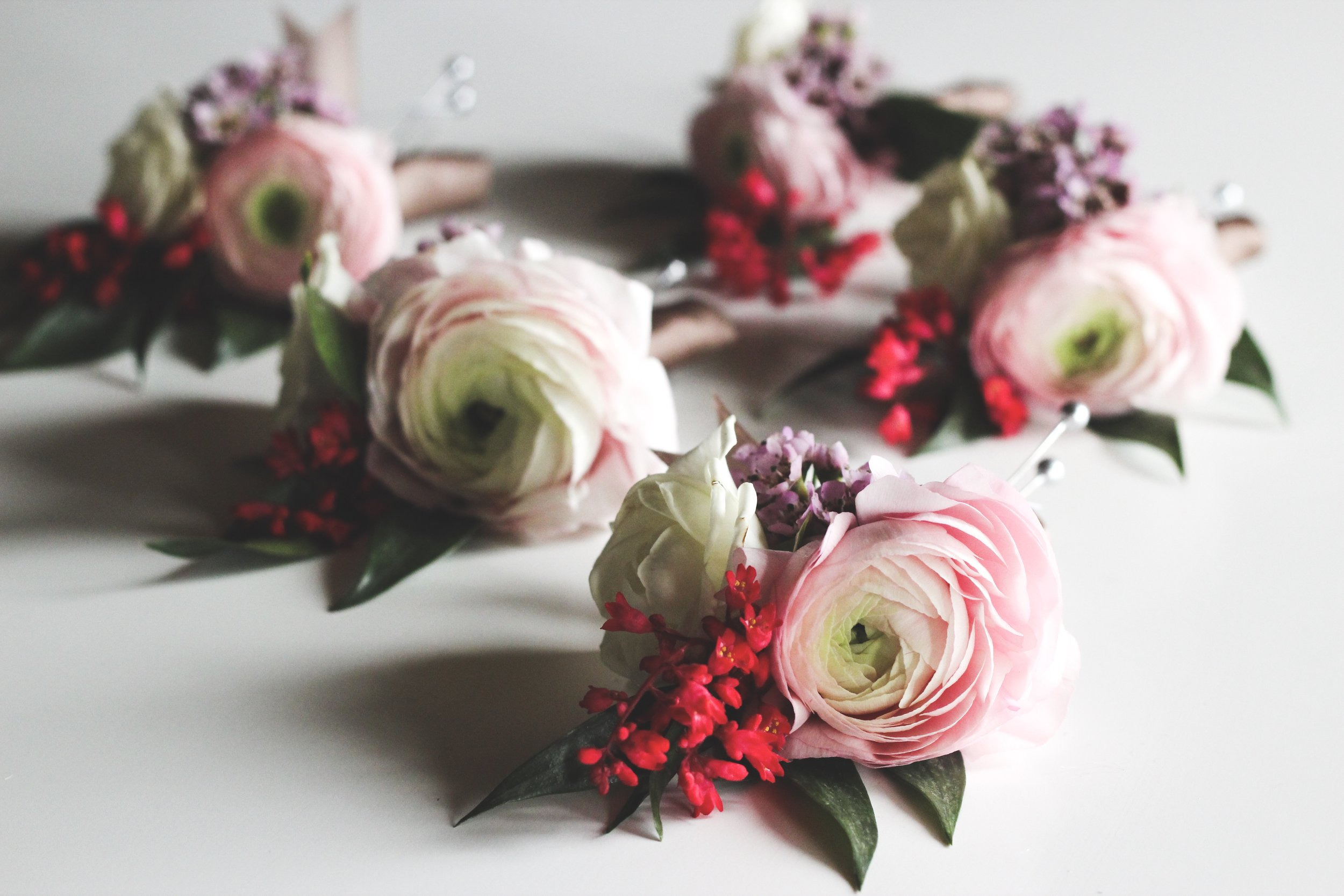 Pink ranunculus, white spray rose and purple wax flower pin on corsage  - Roots & Wildflowers