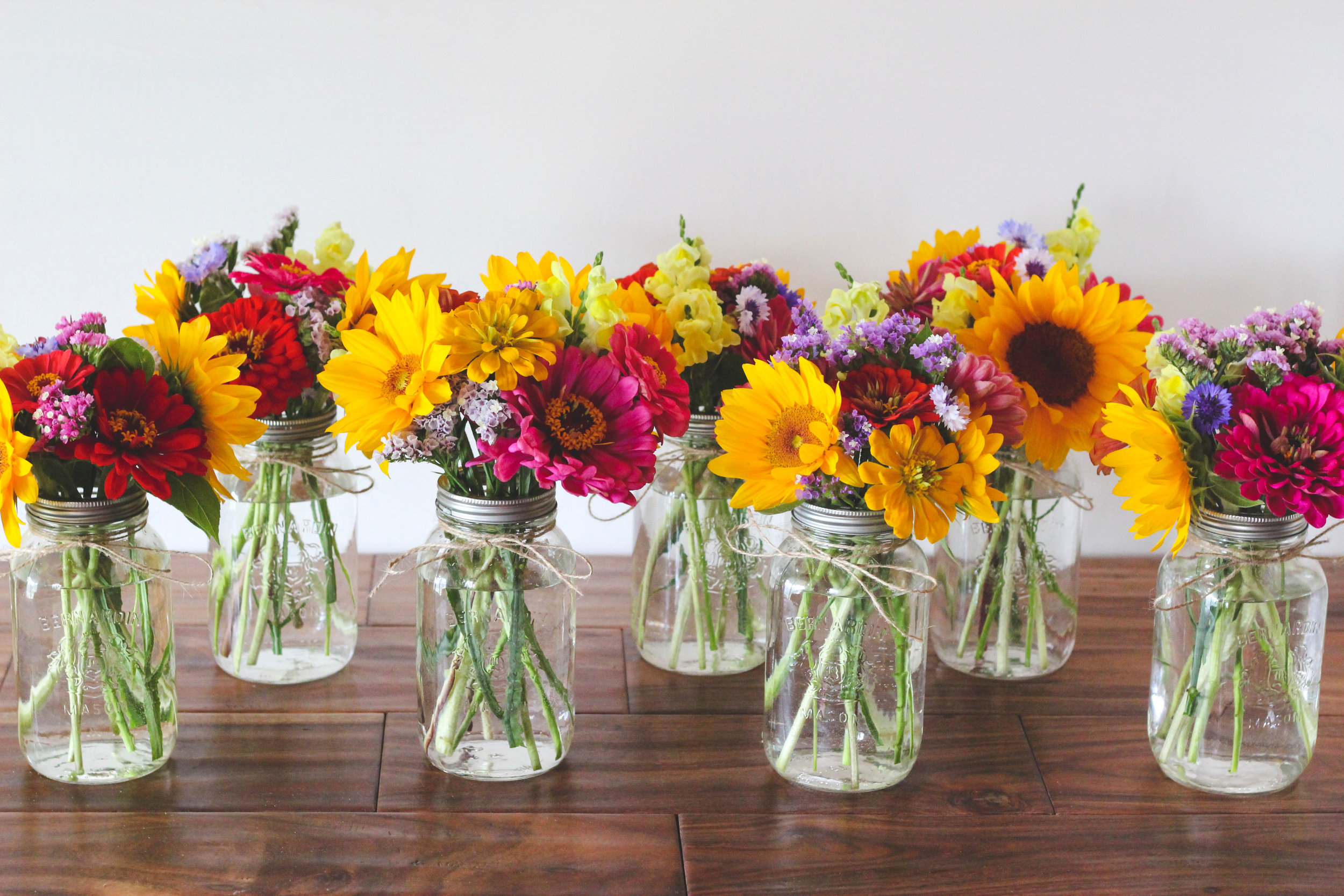 Colourful sunflower zinnia and statice mason jar flower arrangement – Roots and Wildflowers