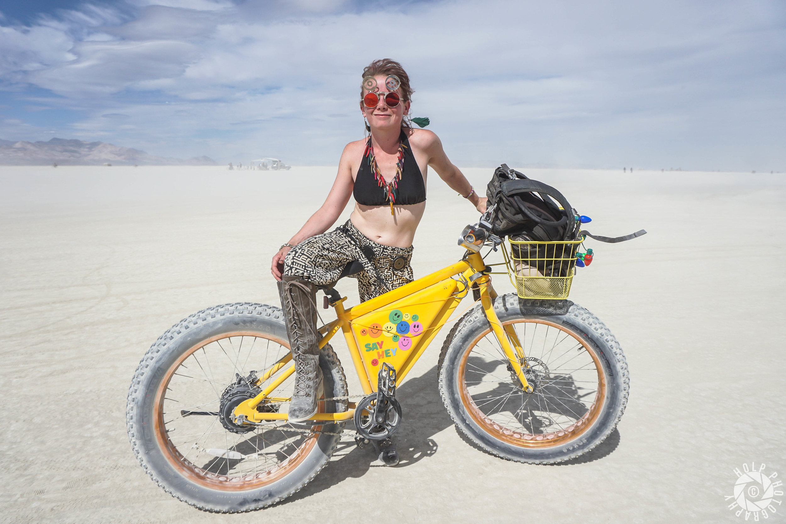 This girl is posing in front of her electric-motor bike on the playa.