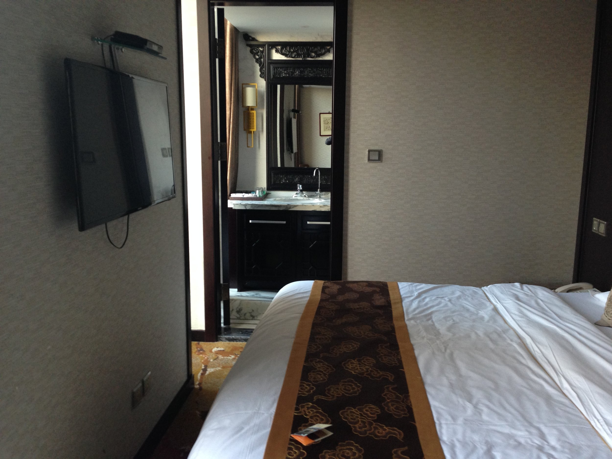 The bed is large, with just enough room to walk by it to the bathroom.