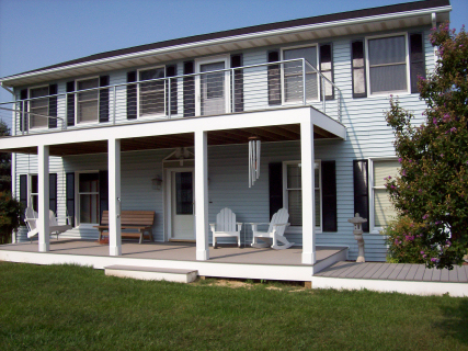 "This home had a second floor deck added. They liked it so much they had Carrion Home Repair add another on the opposite side of the house. These decks are framed with pressure treated 2x10's. The decking is gray evergrain (5/4 x 6in). The decking and columns are wrapped with ""Azek"". A window was removed and an exterior door and Pella storm door was added."