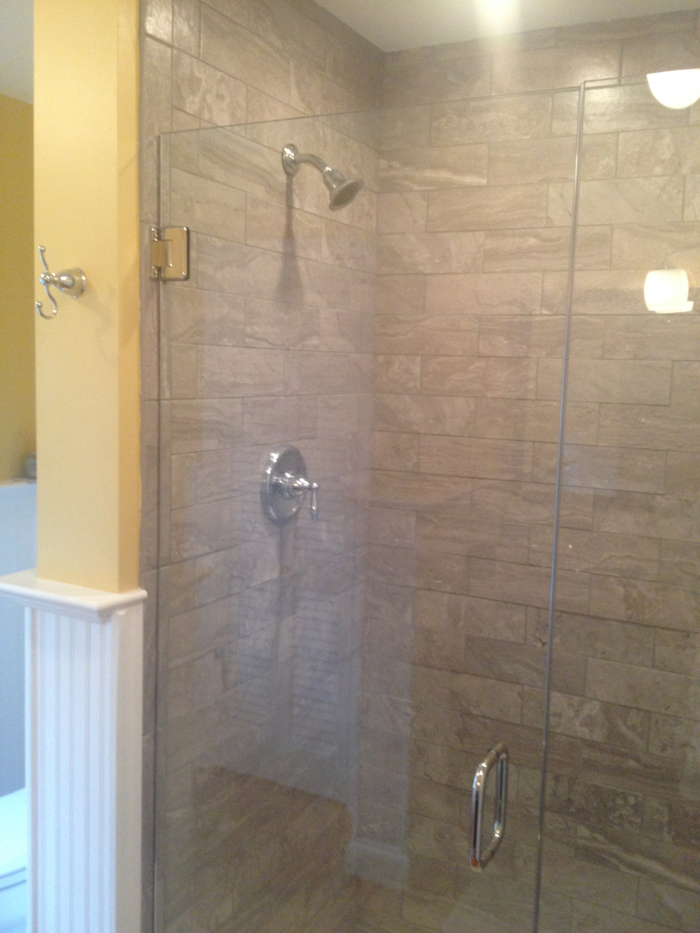 A new tiled shower with a frameless glass enclosure.