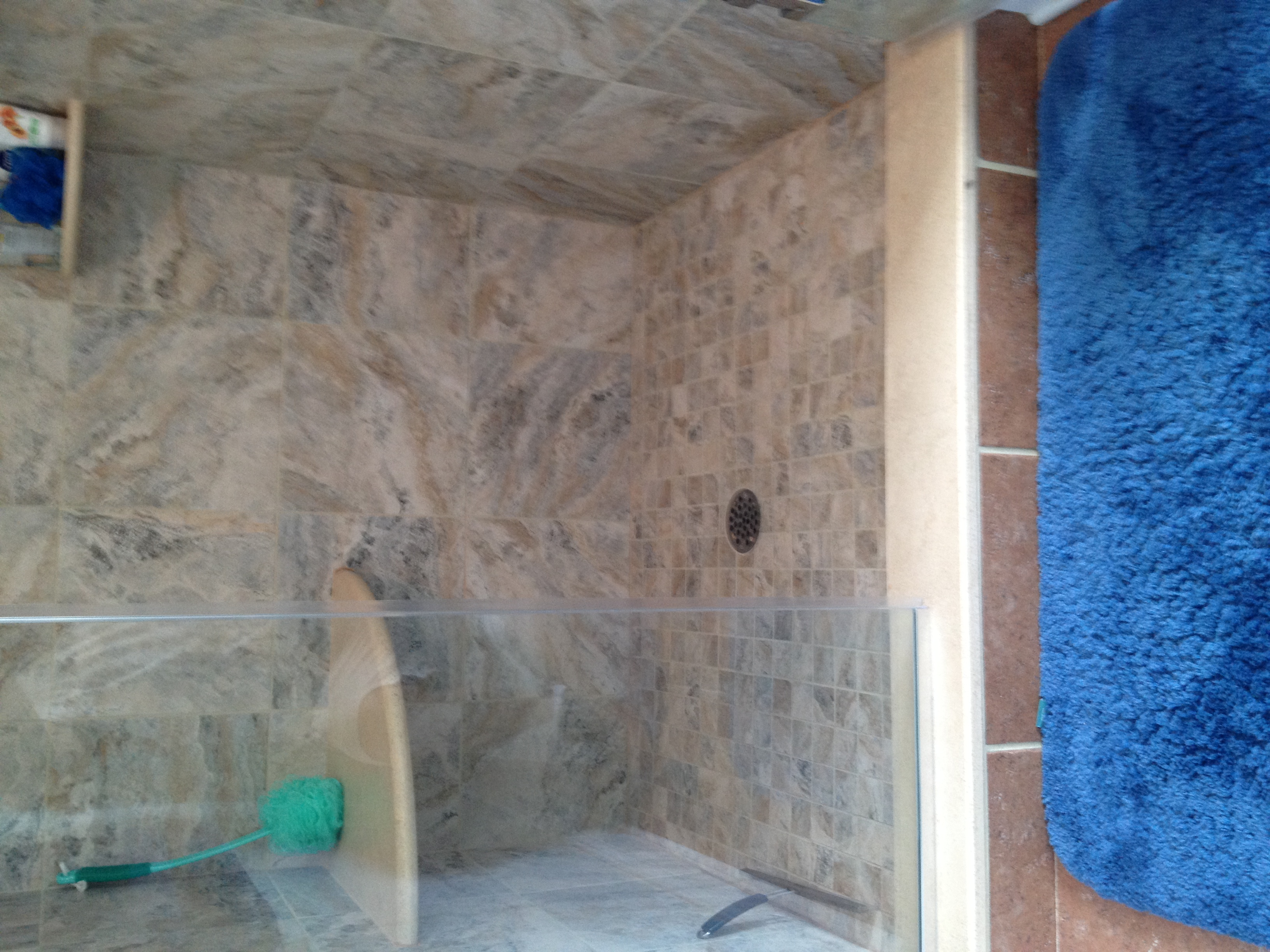A new tiled shower with a frameless glass enclosure