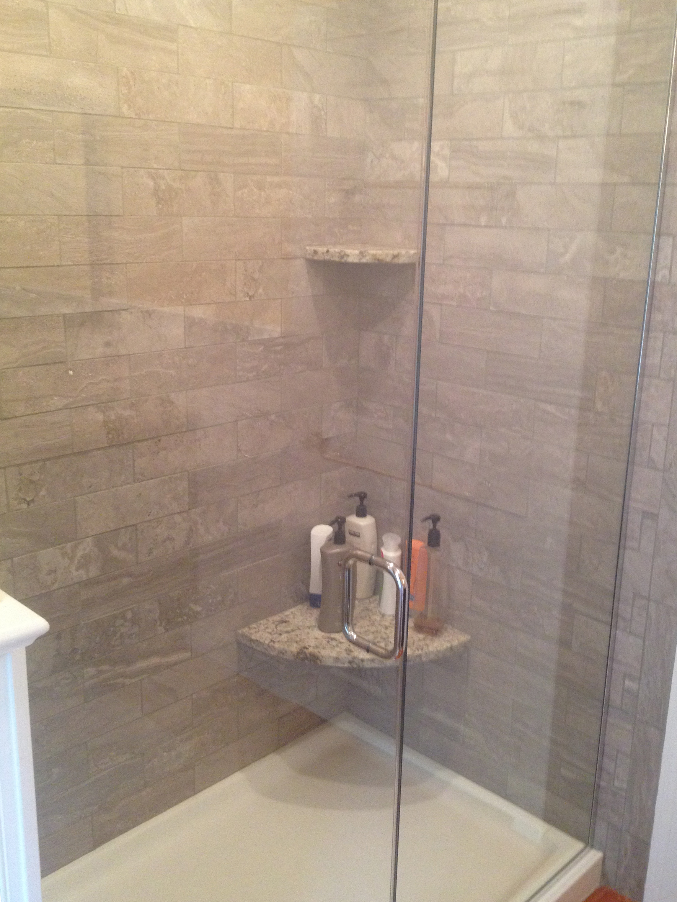 A new tile shower with a frameless glass enclosure.  The granite seat matches the vanity countertop.