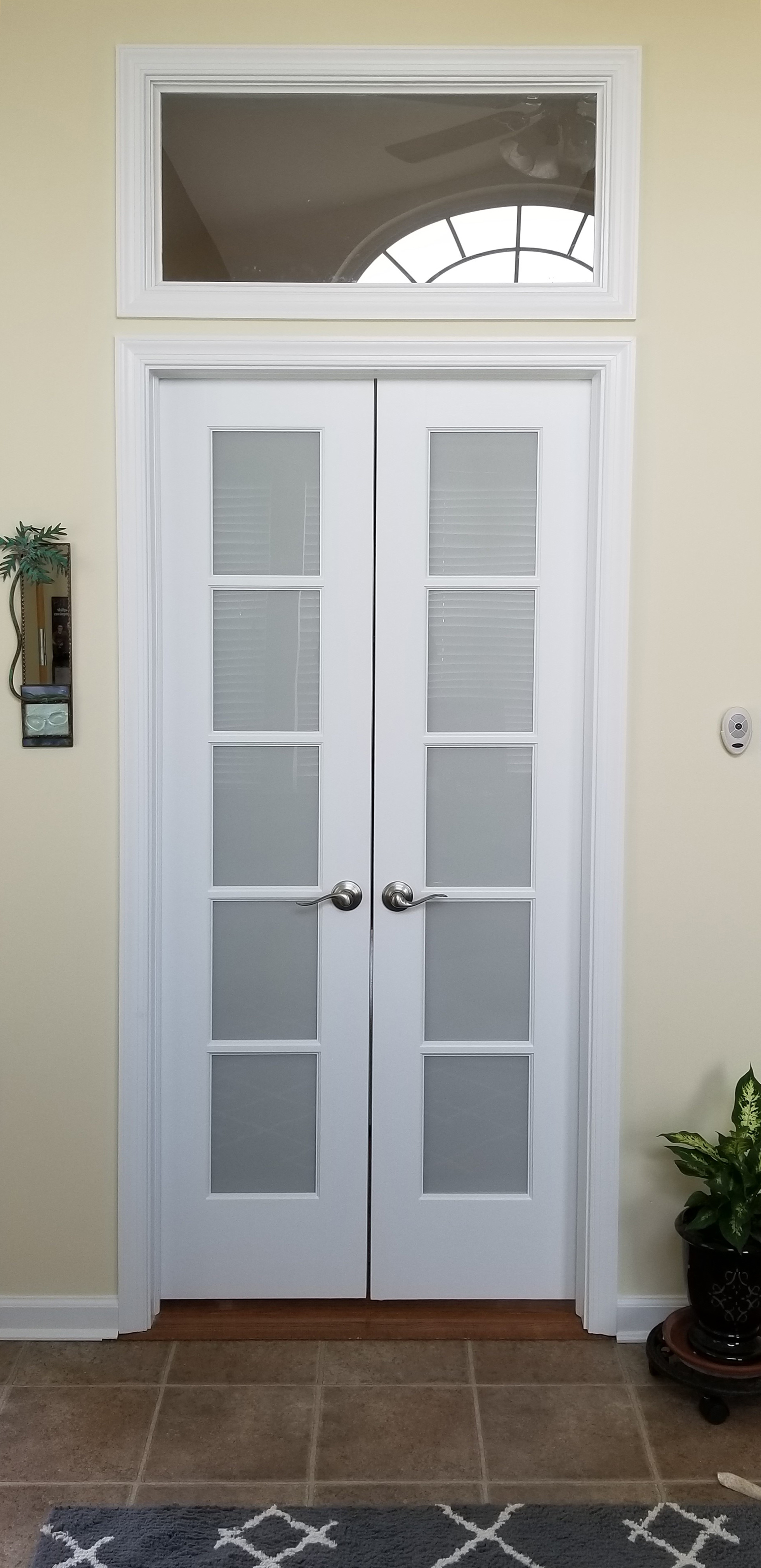 These french style double doors have ball catches at the top and a transom custom window above.