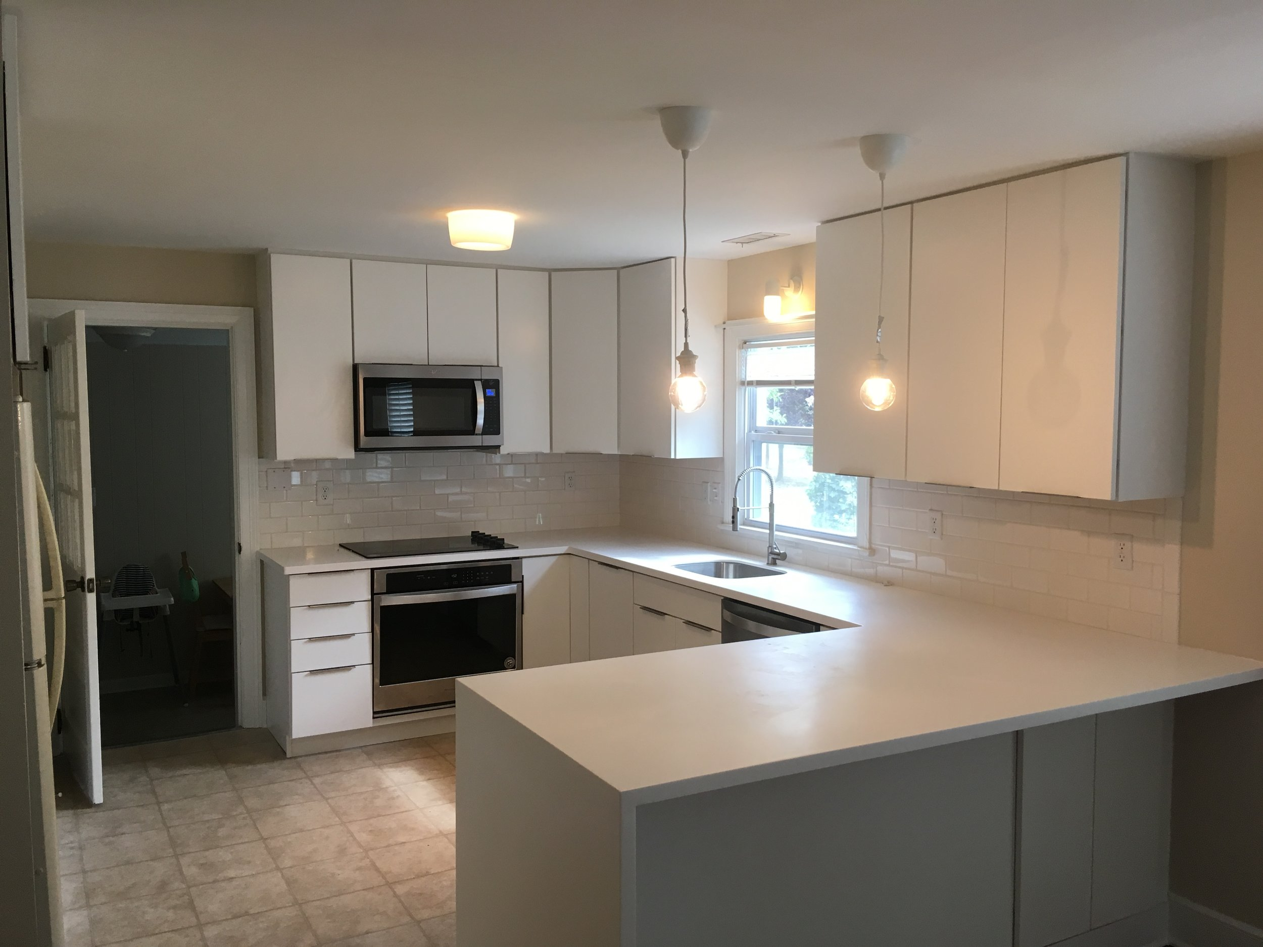 This new kitchen is complete with new Waypoint cabinets and Glacier white corian waterfall countertops.