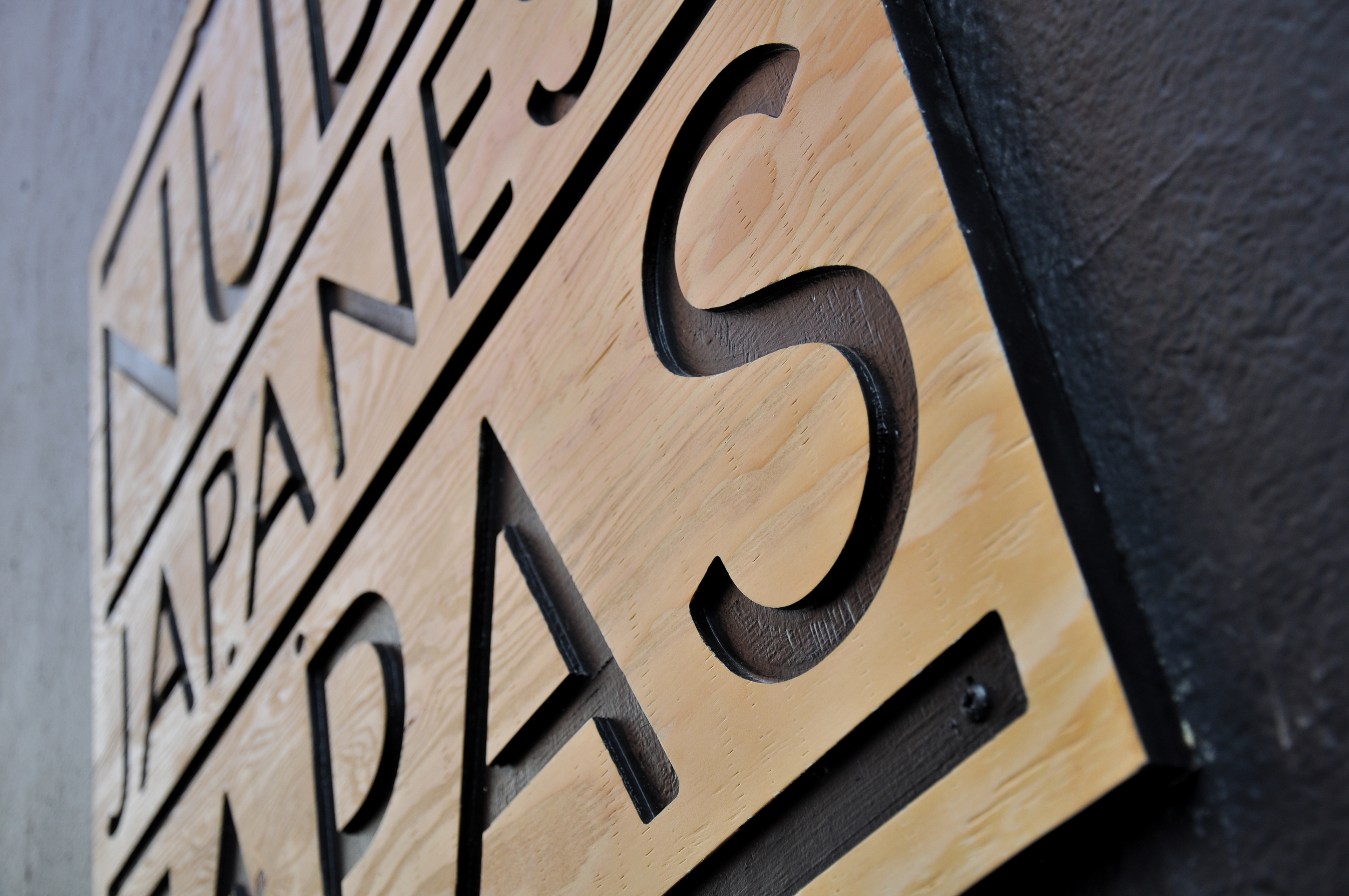 Standard plywood was cut using a CNC router, then painted and sealed. These signs are a welcoming preview of the modern aesthetic that continues inside the restaurant.