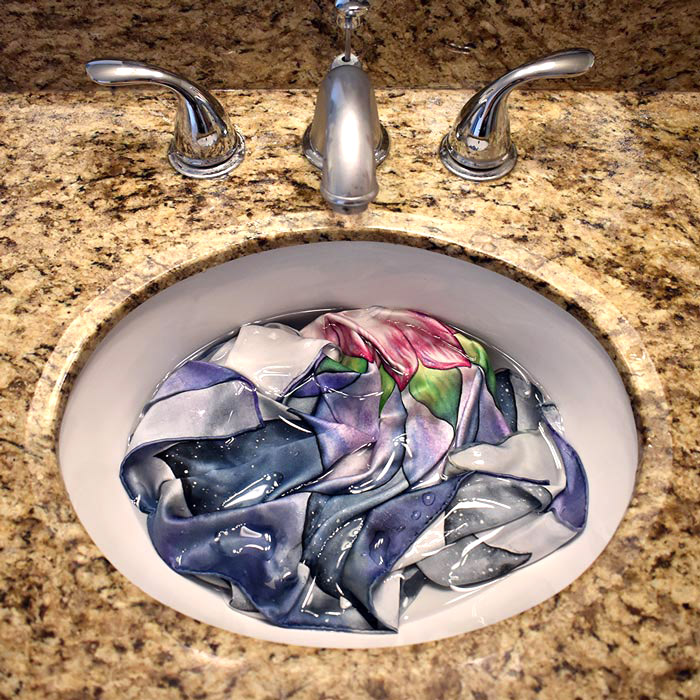 2. - Take your silk altar cloth and soak it well. You'll notice the creases disappear immediately. Once fully soaked, do not wring or twist to remove the excess water. Just hold it up above the sink and let it drip a little.