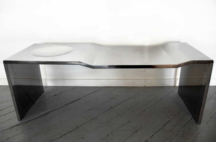 2009  Stainless steel  15-7/10 x 50 x 15-7/10 in (40 x 127 x 40cm)  Bowl Bench Stainless Steel is the metallic version of the hand- sculpted plywood series.    Nature morte bowl series is an homage to the artist's grandmother Anita, who always had a porcelain bowl with porcelain fruit decorating the dinning table. Errazuriz's parents and uncles continued the tradition, and so in an attempt to invite his generation to incorporate this tradition, the artist decided to physically carve out a bowl into the surface of his table. The table itself is also carved out of plywood blocks.