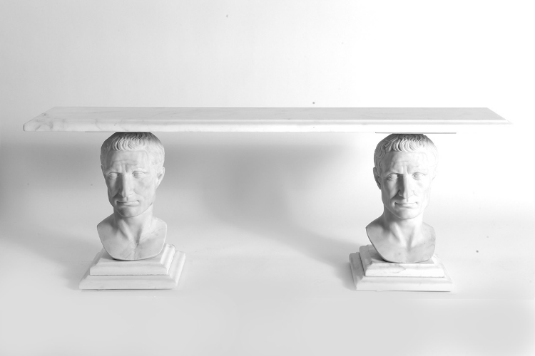 "2013  Marble, Stainless steel component  H: 18 x W: 48 x D: 10 in (45,7 x 121,9 x 25,4cm)   The Caesar Bench created by artist Sebastian ErraZuriz was originally named: ""Empires will fall, heads will roll"". Julius Caesar depicted in the bench was famously remembered for transforming the Roman republic into the Roman Empire and becoming the first dictatorship until he was murdered and his reign was toppled.   The bench, was designed to be exhibited at the Fairchild Gardens. When Sebastian originally saw photographs of the lavish privately owned gardens and adorned by sculptures they reminded him of a tropical version of the luxurious gardens of Versailles where during the French revolution the rebels entered the gardens and their sculptures narrowly escaped being broken down and being melted into ammunition to fight the revolution.   The use of Julius Caesar's busts as mere cinder blocks for people to sit in an almost profane and mundane way invites the viewer/user to remember today's empires and leaders will most surely be toppled tomorrow."