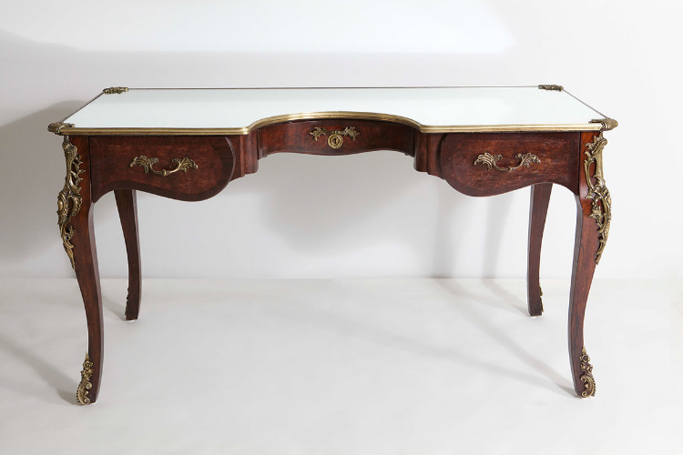 """2013  Found antique desk of mahogany, walnut and bronze in form with mirroed glass top  32 3/4 x 59 x 26 3/4 in (83,2 x 149,8 x 67,9 cm)  The Narcissus Desk is a new piece by the New York based artist and designer Sebastian ErraZuriz. The desk is a continuation of his functional sculptures, which invite the viewer to look again at everyday objects, spaces and situations.  The Narcissus desk was originally inspired by Caravaggio's painting of Narcissus that Sebastian remembers seeing as a child with his father, an art teacher, while on a trip to Italy. The artist explains: """"I was struck by the idea that someone could see their reflection and yet not be aware they were looking at themselves. I believe today we are becoming like Narcissus; so obsessed with our own perfectly edited online self that we forget to be aware of the real """"me"""" outside the screen.""""  The desk wishes to offer the user a moment of reflection, a moment of thought at the one space where we make most of our important decisions in life. In order to fabricate the desk, Sebastian found a broken down French Desk from circa 1880, which he then completely restored. He cut into the original desk with a semi circumference to allow the user to now fit inside the desk. The original top was replaced with a mirror."""