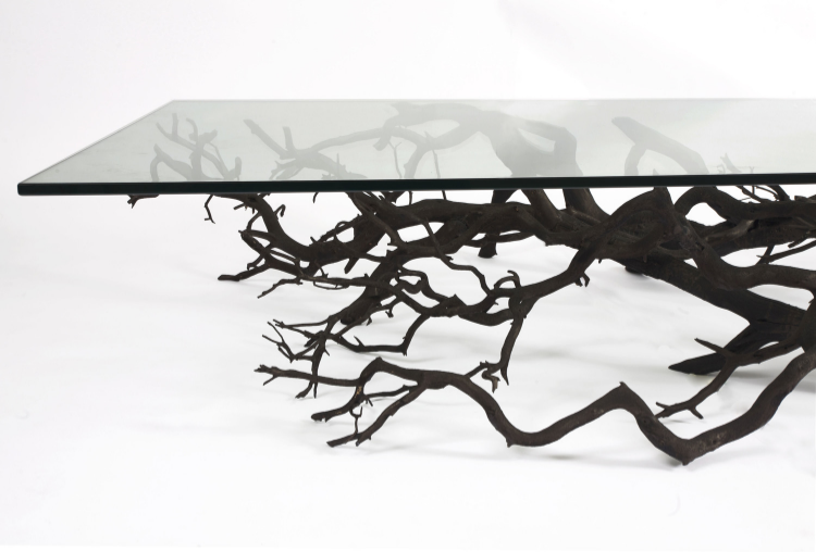 2010  Real tree, carved wood, natural dyes, steel and tempered glass  Dimensions variable  For centuries we have used wooden boards to create furniture. The Tree Table created by New York based artist and designer Sebastian ErraZuriz, proposes that no matter how beautiful or sophisticated our furniture designs might be, the shapes we can find in nature are often more mysterious and intriguing.  Rescuing fallen, dead native trees from forests in South America, Sebastian ErraZuriz twists and readapts their branches so they can find a new life as sculptural and functional pieces.