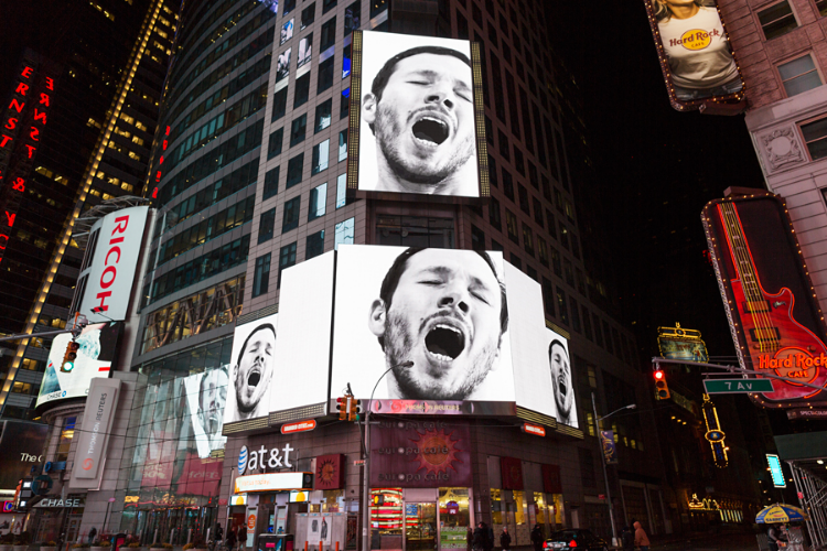 """The 3-minute video by Sebastian ErraZuriz contrasts with its environment by being extremely slow paced and filmed exclusively in black and white. There are no camera movements, no editing cuts and no motion graphics. The video portrays a close up of the artist slowly looking around him and yawning multiple times during the whole duration of the video. The simultaneous projections of slow black and white images of the yawning figure dominate and momentarily transform the environment of Times Square. Many of the visitors looking at the screens find themselves suddenly coerced into joining the artist in yawning, consequently getting others around them to contagiously yawn too.  The video can be interpreted as a peaceful and personal act of protest by the artist against the overwhelming market system that he is surrounded by. The contagious character of the yawn video seems purposely designed to get others to yawn with him and appear as if they had voluntarily gathered every night to join the artist in his protest.  Sebastian ErraZuriz expressed that he hopes the video can offer a brief moment of pause that can remind us of our urgent necessity for free space and time that can allow us to recover a stronger sense of awareness. When asked if the project was strictly criticizing the market, he expressed he also finds himself tired of how the art market in influencing much of the current artistic production. """"I'm yawning at everything and all of us; we need to wake up"""""""