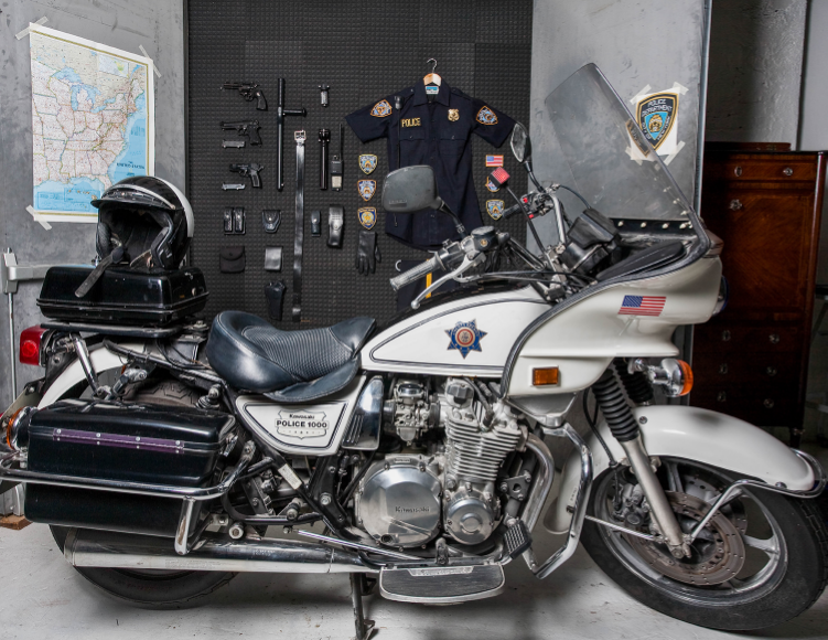 2009  Found police objects, motorcycle, wood and acoustic panels   Sebastian ErraZuriz searched for and purchased the elements that comprise a complete United States police uniform on various internet sites for almost two years. The collected objects, tools, badges, and weapons allegedly came from former policemen and other ex-law enforcement professionals who had retired and sold their belongings online. Once the artist finally completed the full collection, it was displayed like a movie arsenal behind a couple of secret doors installed in his studio. The art installation calls to mind the secret rooms in which superheroes hide their identities or sociopaths plan their robberies.  For the artist, this installation highlights how easily a common citizen can legally acquire a full policeman's uniform, allowing that person maximum authority and power on the streets.