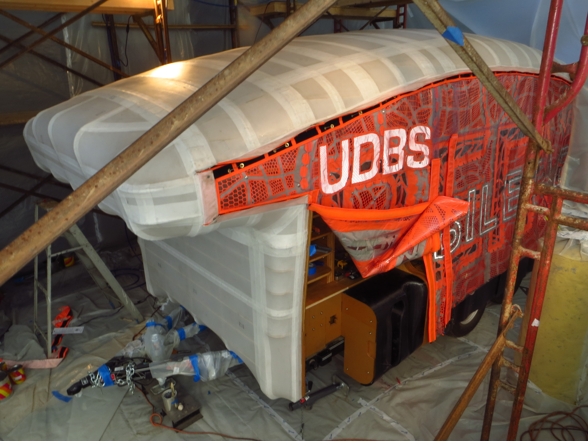 Poly-fiber roof fabric was patterned, adhered, stitched to ribs, and coated with weatherproofing and paint.