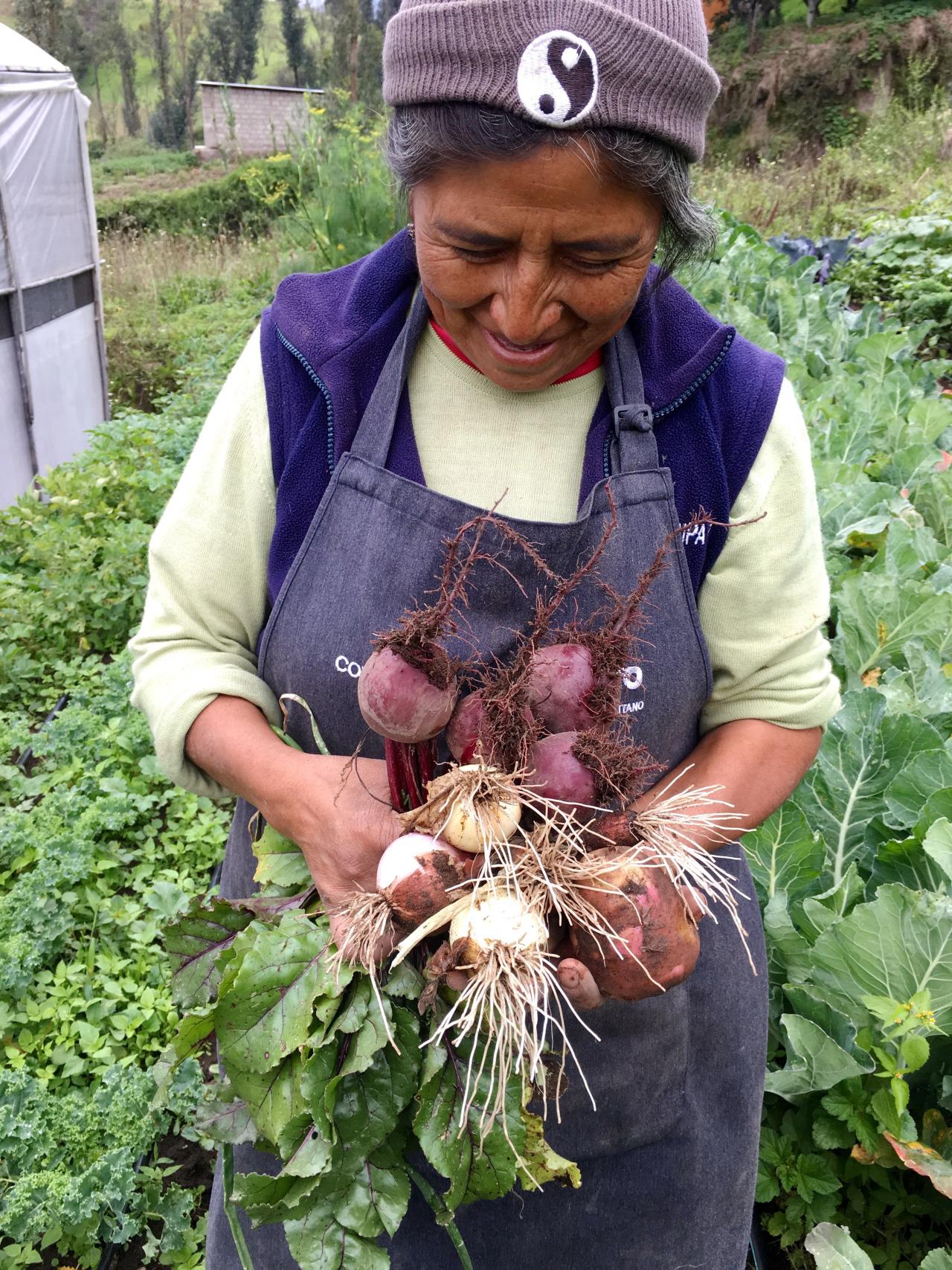 Señora Elvira with a bouquet of vegetables from her garden