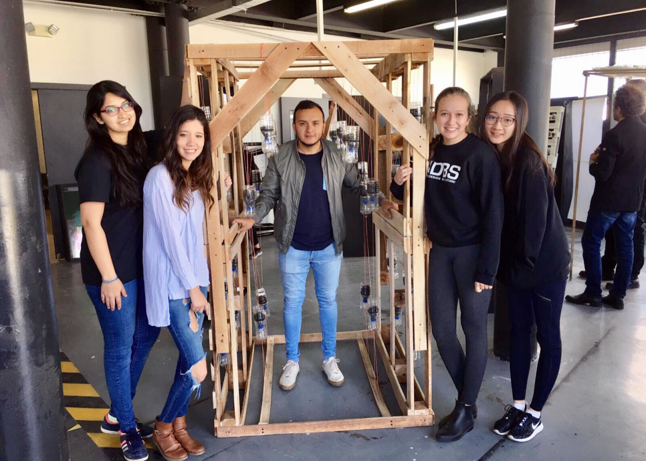 A student group shows off their prototype made from waste string, bottles and wood pallets.