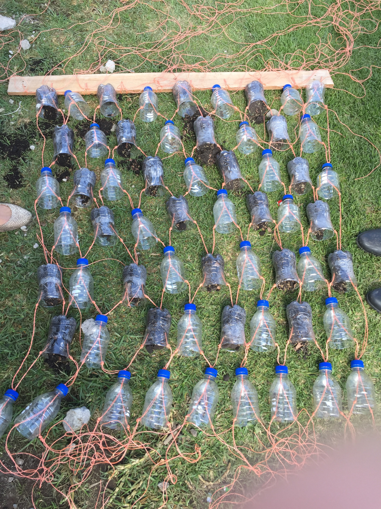 """The """"Cortina de Agua"""" prototype was built with reconstituted plastic bottles, string, PVC pipe, and wood from a deconstructed pallet. It can be made by one person using a hammer, a nail, and a knife."""