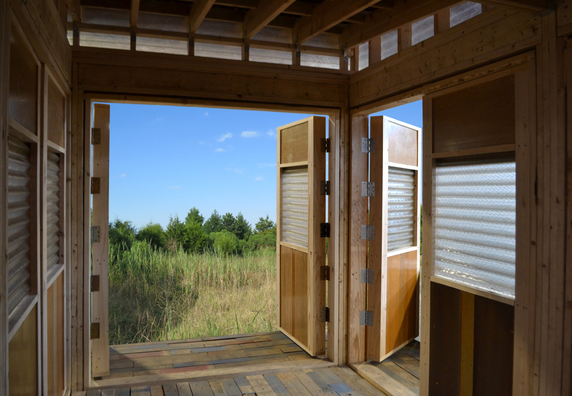 Five sets of doors can be opened to connect to the site. Waste materials include salvaged corrugated glass, pallet slats, church pews, door hinges, and corrugated translucent plastic.