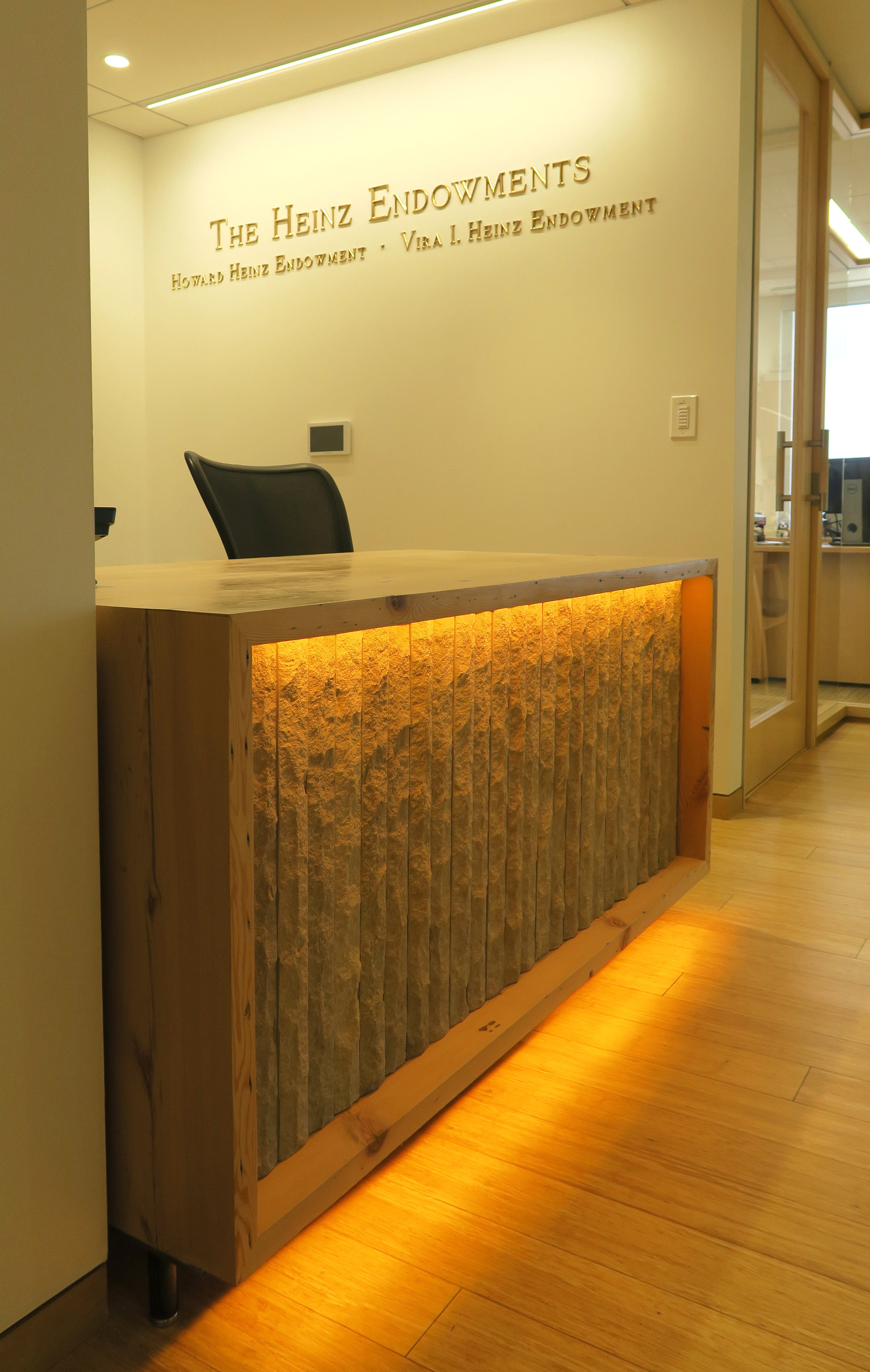 Reception desk is made of chiseled overstock limestone and reclaimed lumber deconstructed from an 1870's lodge