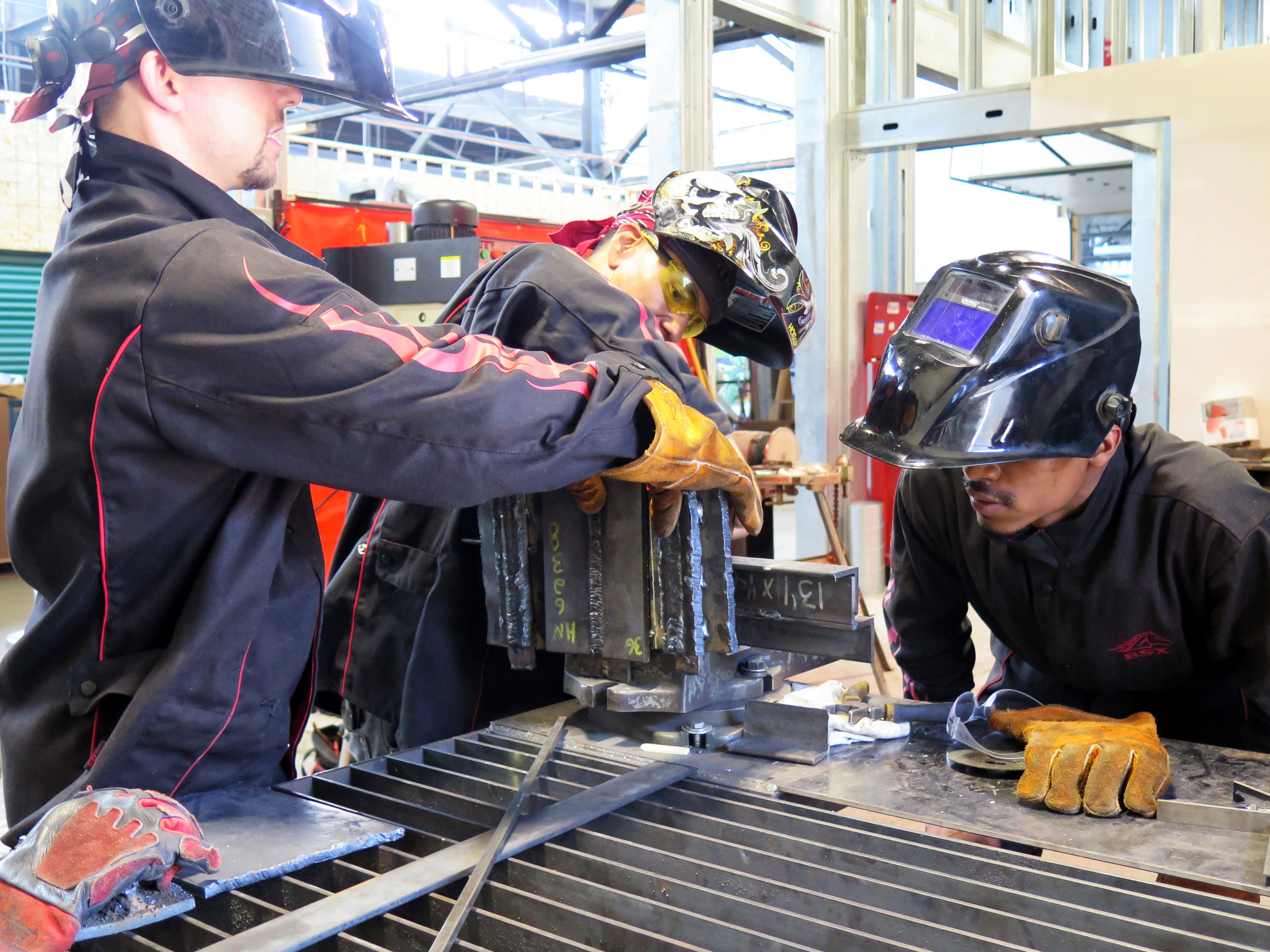 Welding apprentices in training work with a welding instructor on an early mock-up