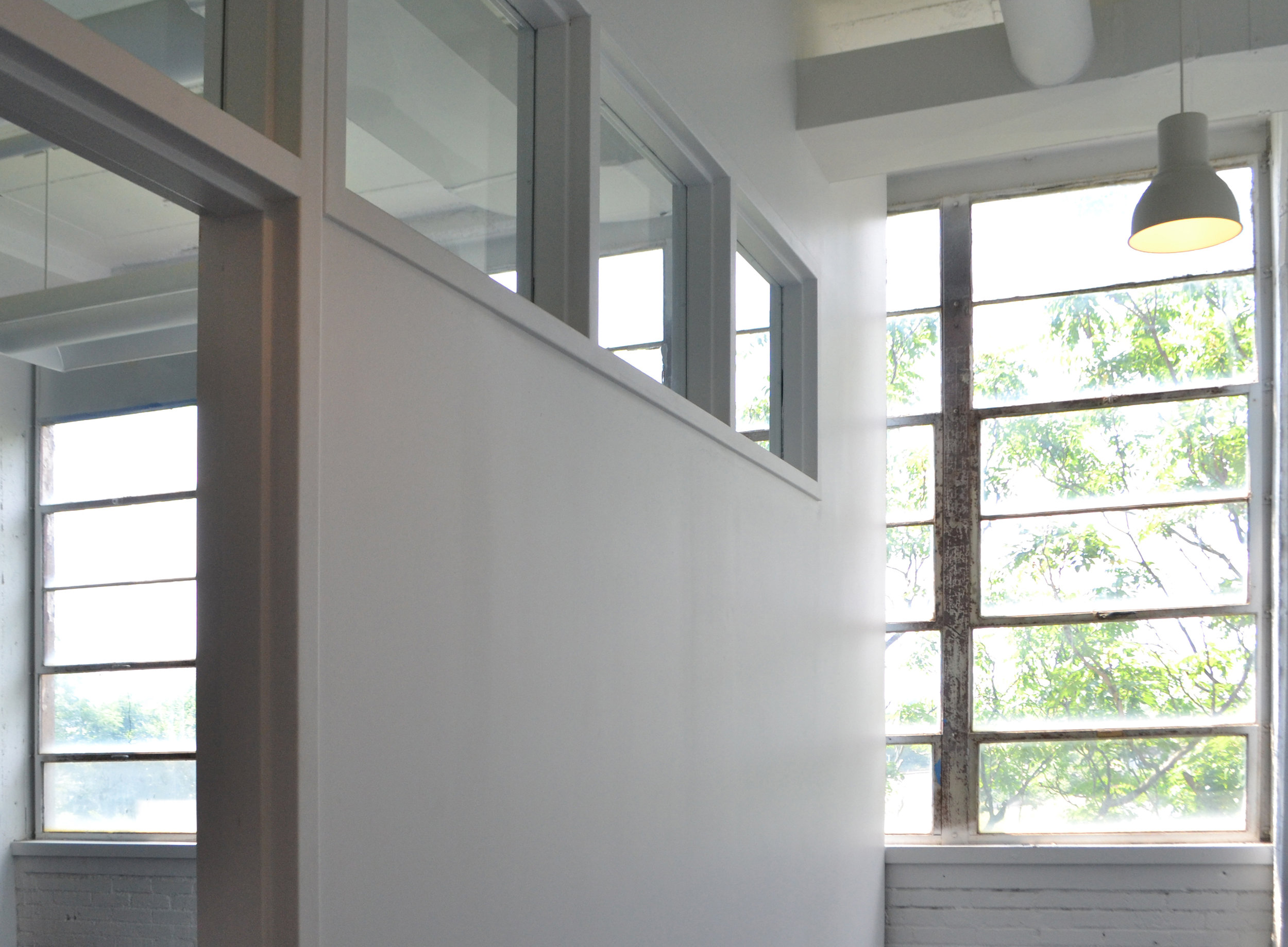 Stock transom windows take advantage of light from existing large industrial windows