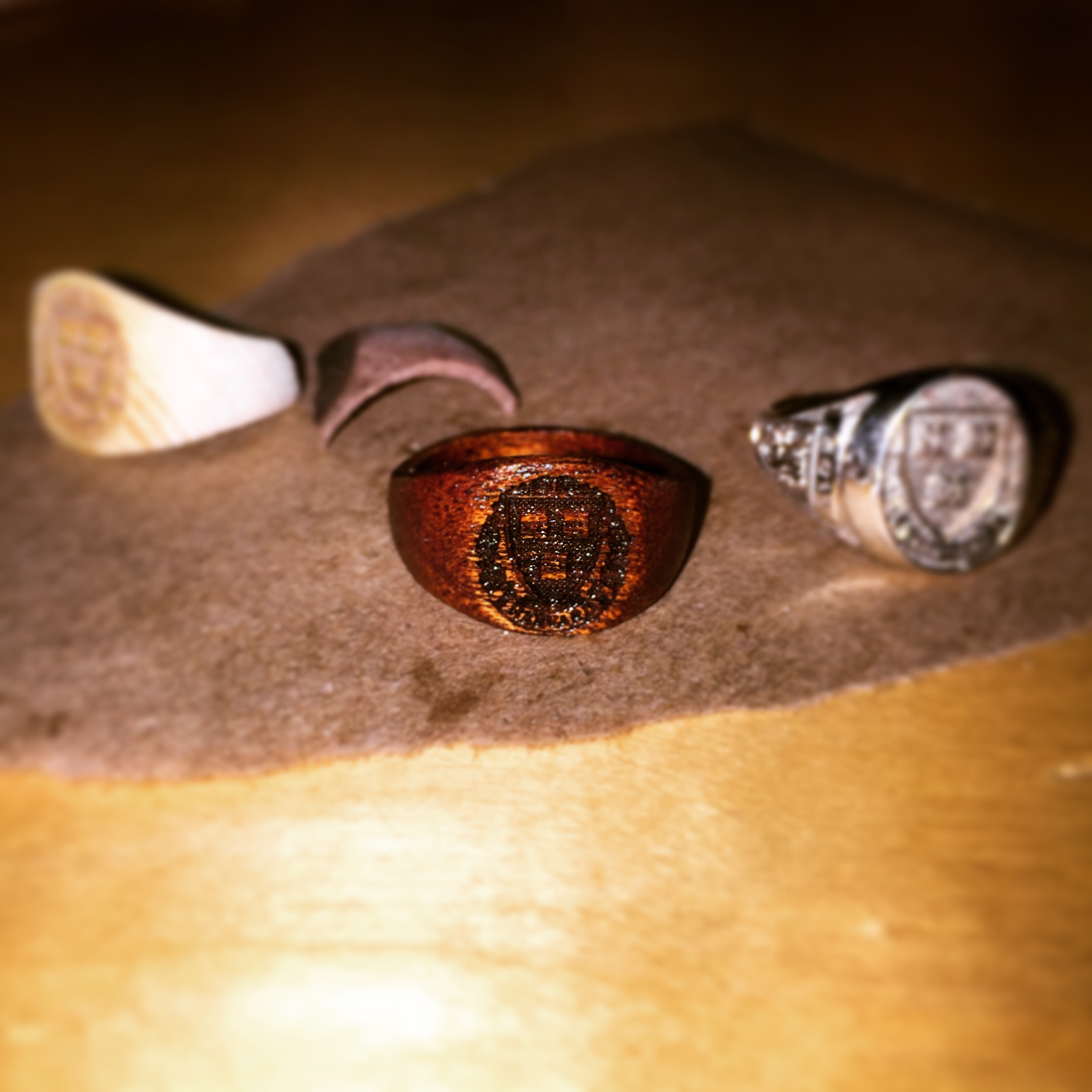 Week 3: The final ring, pictured next to an actual class ring on the right. I went through three different iterations of the ring, two of which are pictured here, before creating the final version out of mahogany. As you can see, I encountered problems when I used soft woods [cherry and pine], when creating the ring; mahogany was strong enough to maintain its shape without cracking, even in the delicate shape of a ring. The final ring was sanded down with extra fine sandpaper and mineral oil to give it the almost goldensheen pictured here.