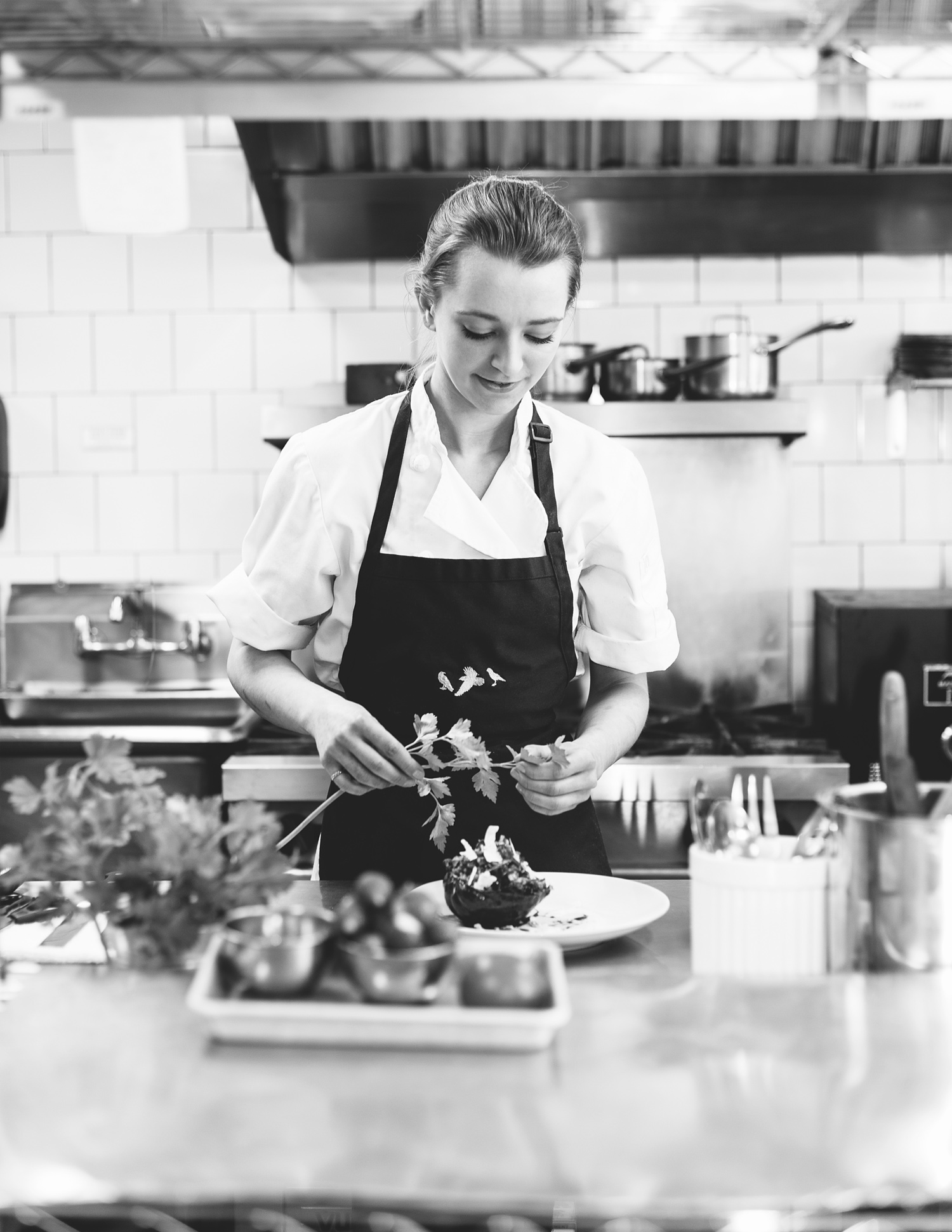 Sous Chef Rose Valentine preparing a dish in the kitchen of 3Crow in Rockport ME