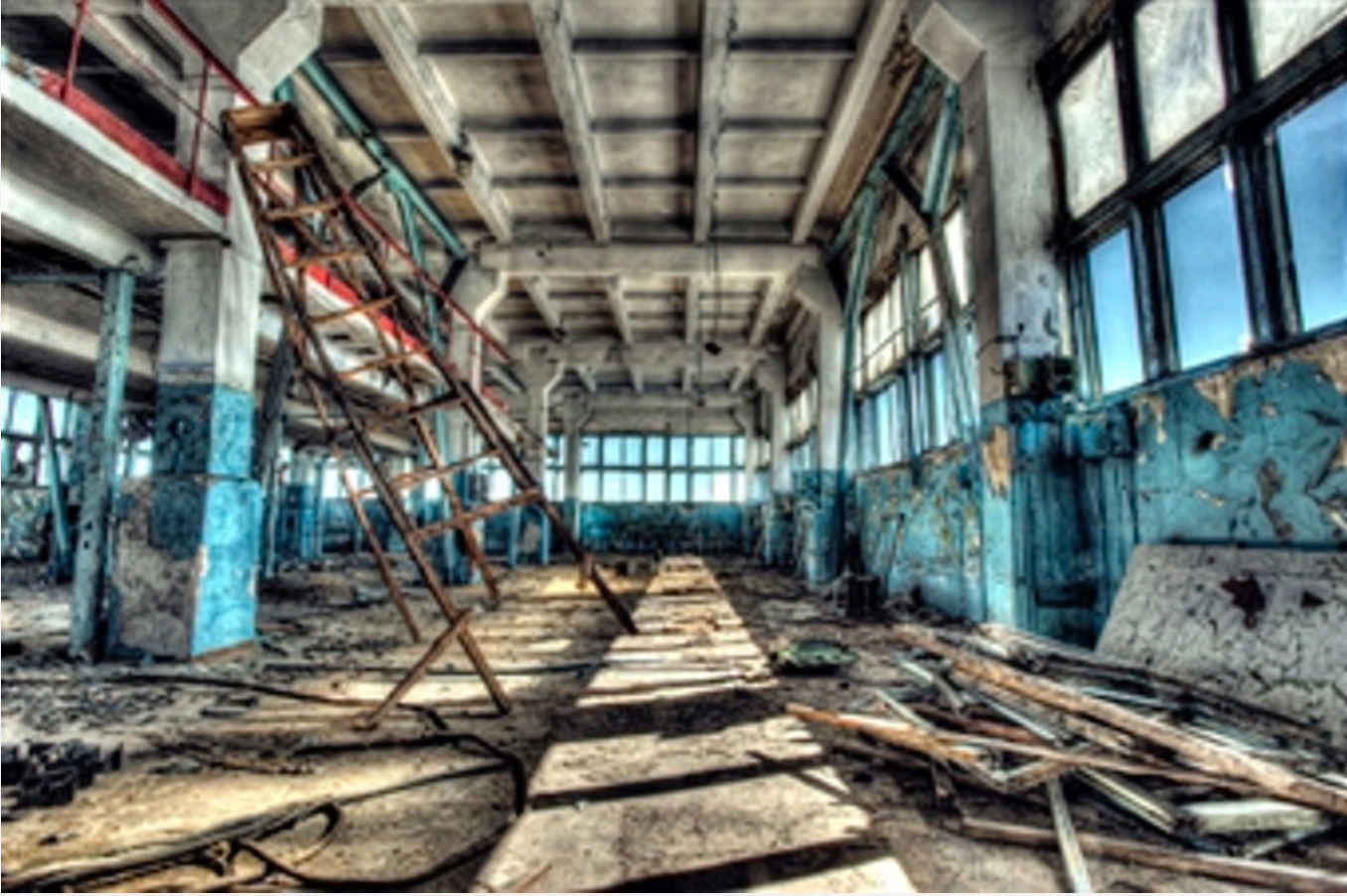 Empty factory floor with falling ladder left of center. This image represents all personal injury.