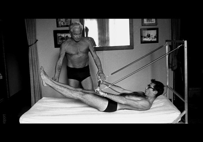 Joseph pilates instructing student on apparatus