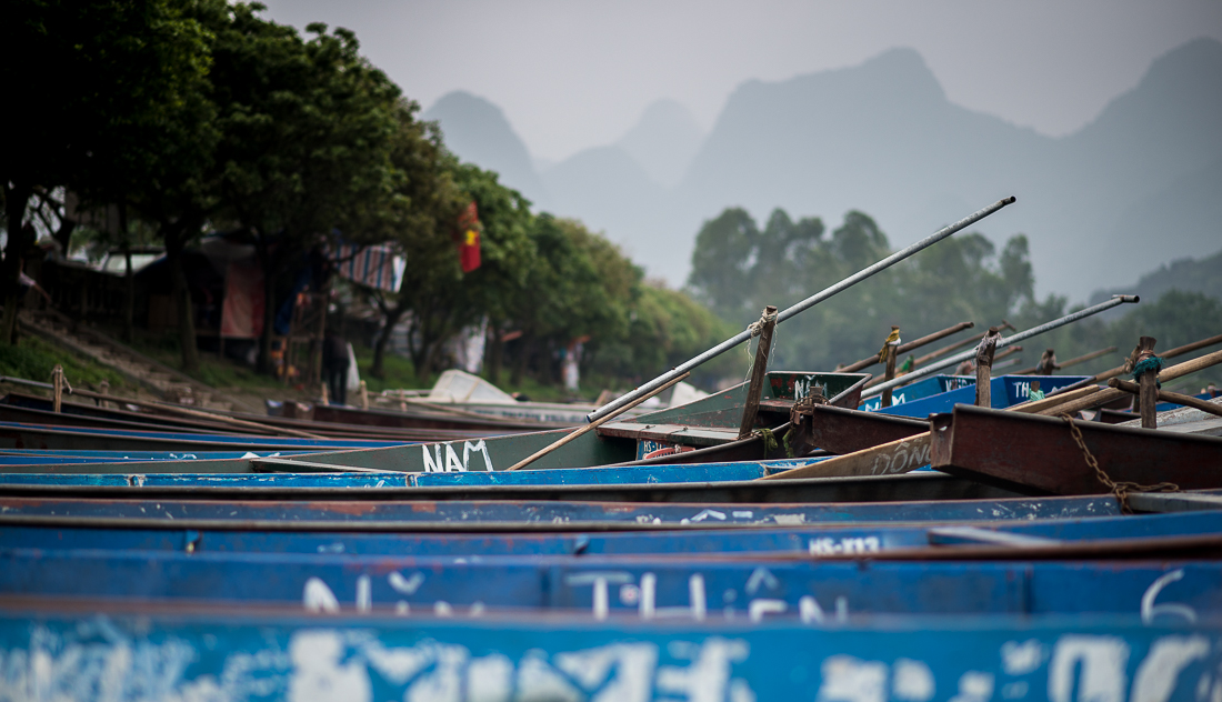 Boats lined up on the river ready to take people to the Perfume Pagoda.  Hanoi, Vietnam