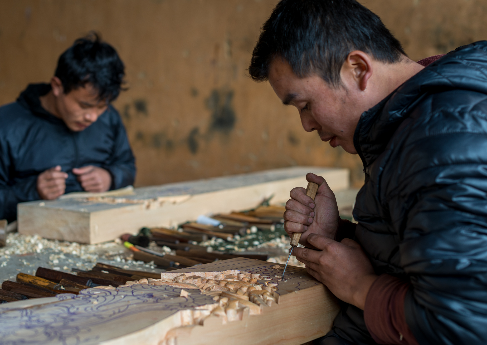 Artists working on replacement wood carvings for the temple