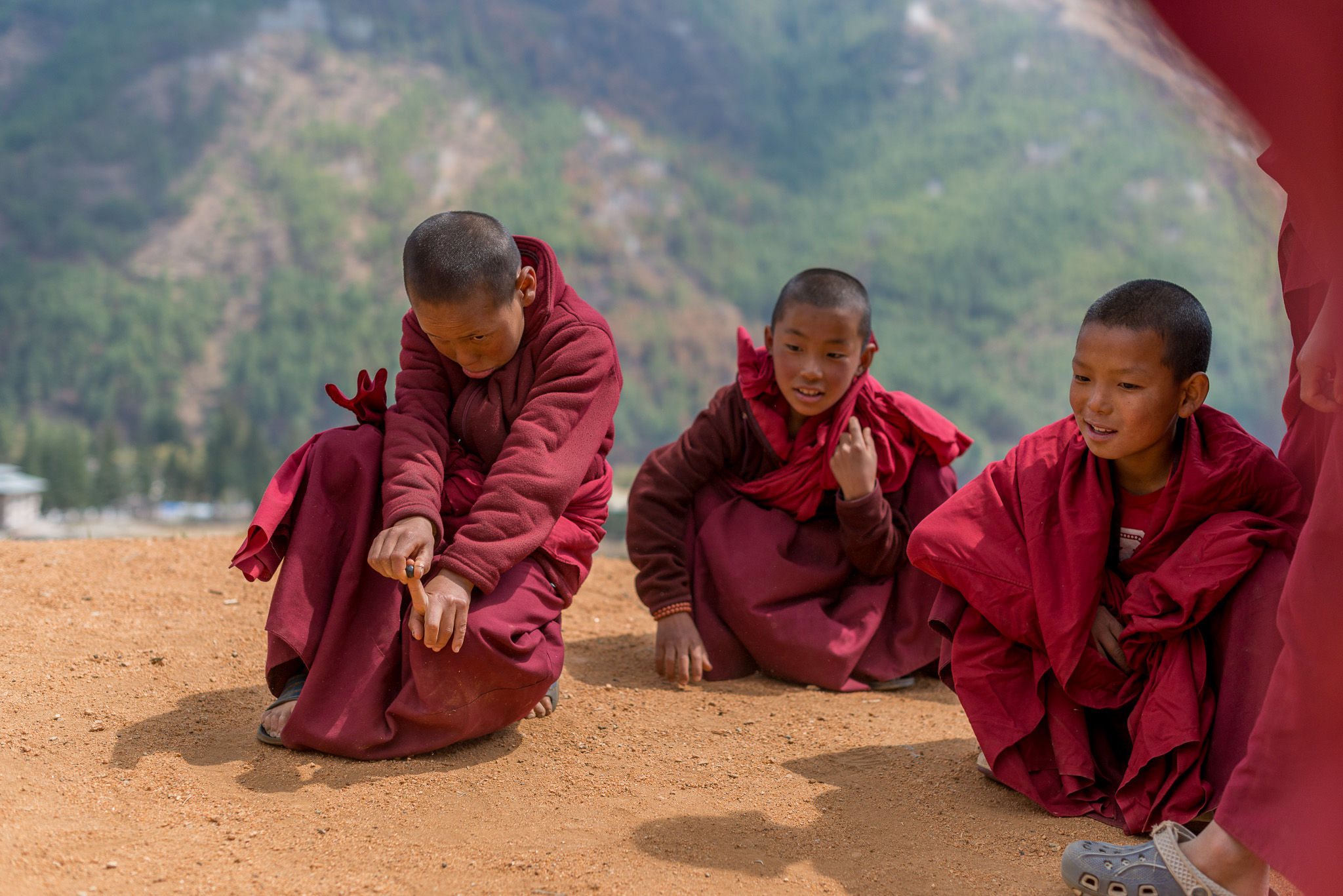 Young Monks playing a game of marbles
