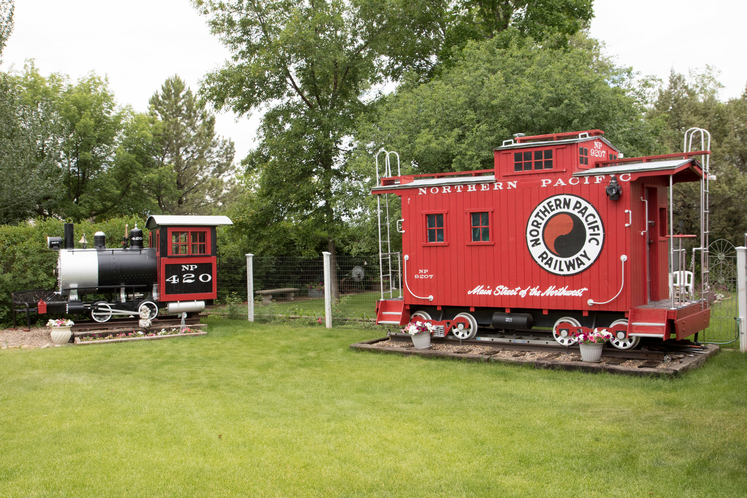 In Hall's front yard, a local landmark, sit two custom built train cars.