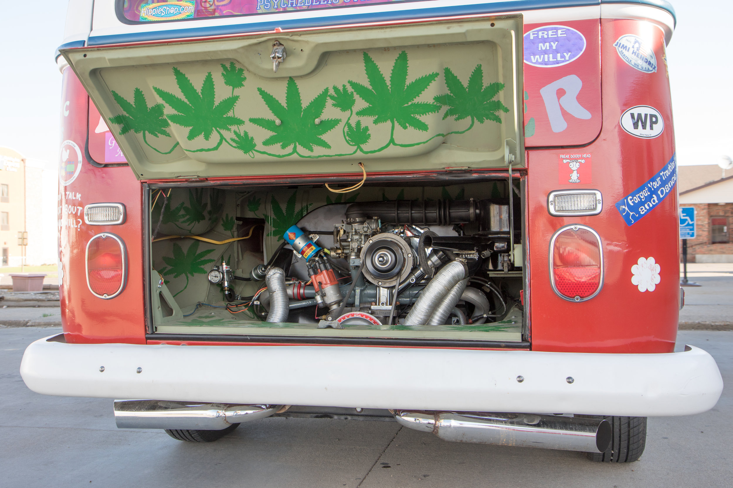 Hand-painted marijuana leaves dot the cramped engine compartment of the VW bus.