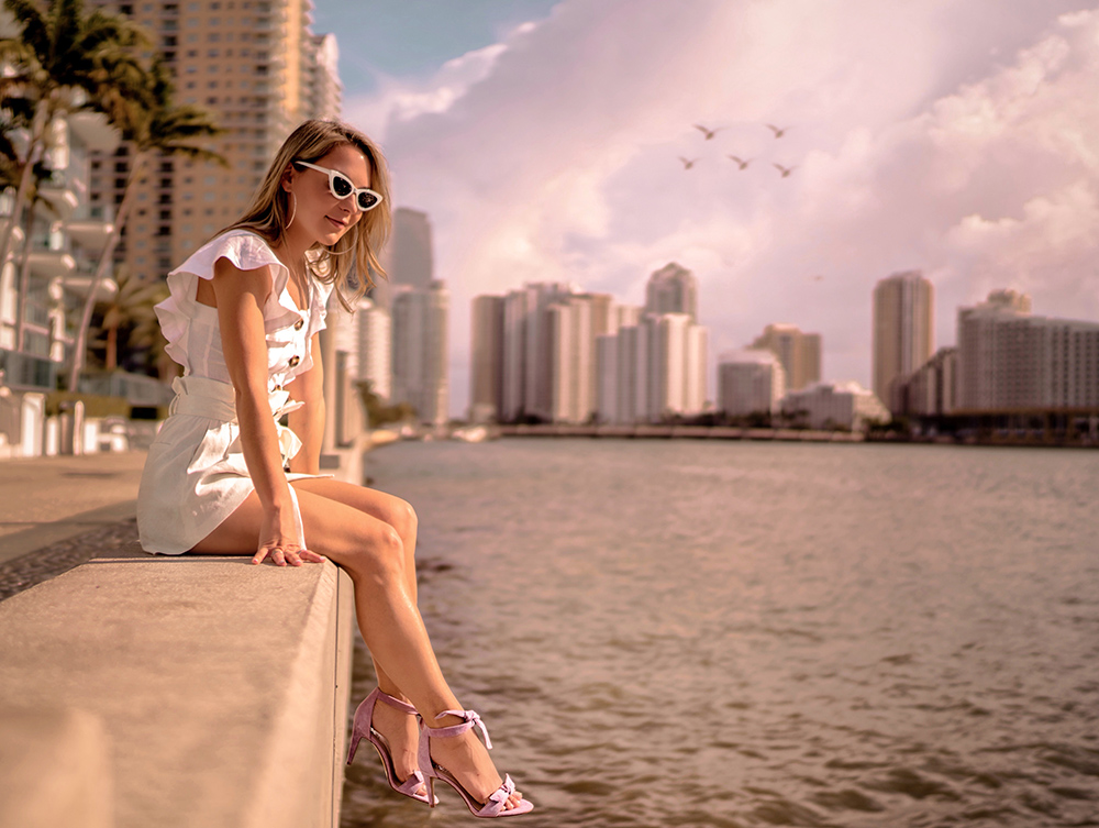 Christie ferrari in miami wears DSW lavender heels and white linen top and shorts in brickell key