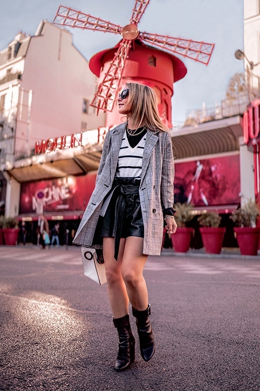 Christie Ferrari wears plaid blazer, faux leather shorts, black leather boots as a runway look for less in Paris, during Paris Fashion Week.