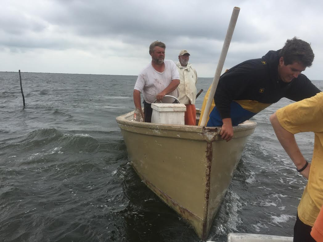 Eddie Willis steers his handmade boat with his son at the front