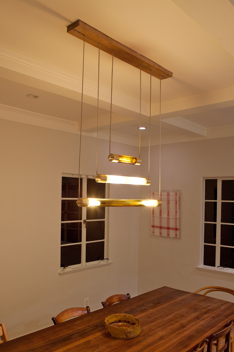 A set of 3 chandeliers, installed on their wood base.