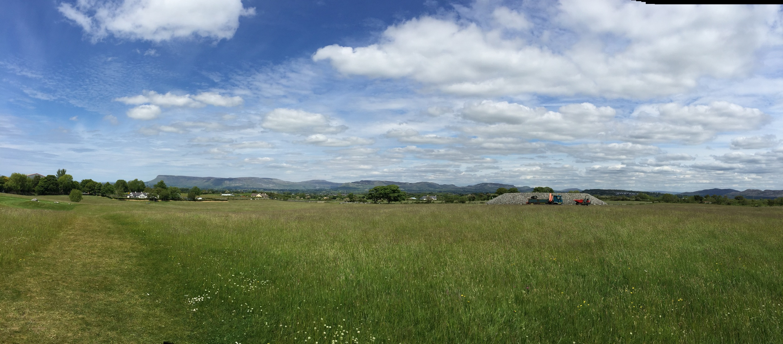 Again, in the middle of a field, like Hill of Tara, mountains dotting the distance.