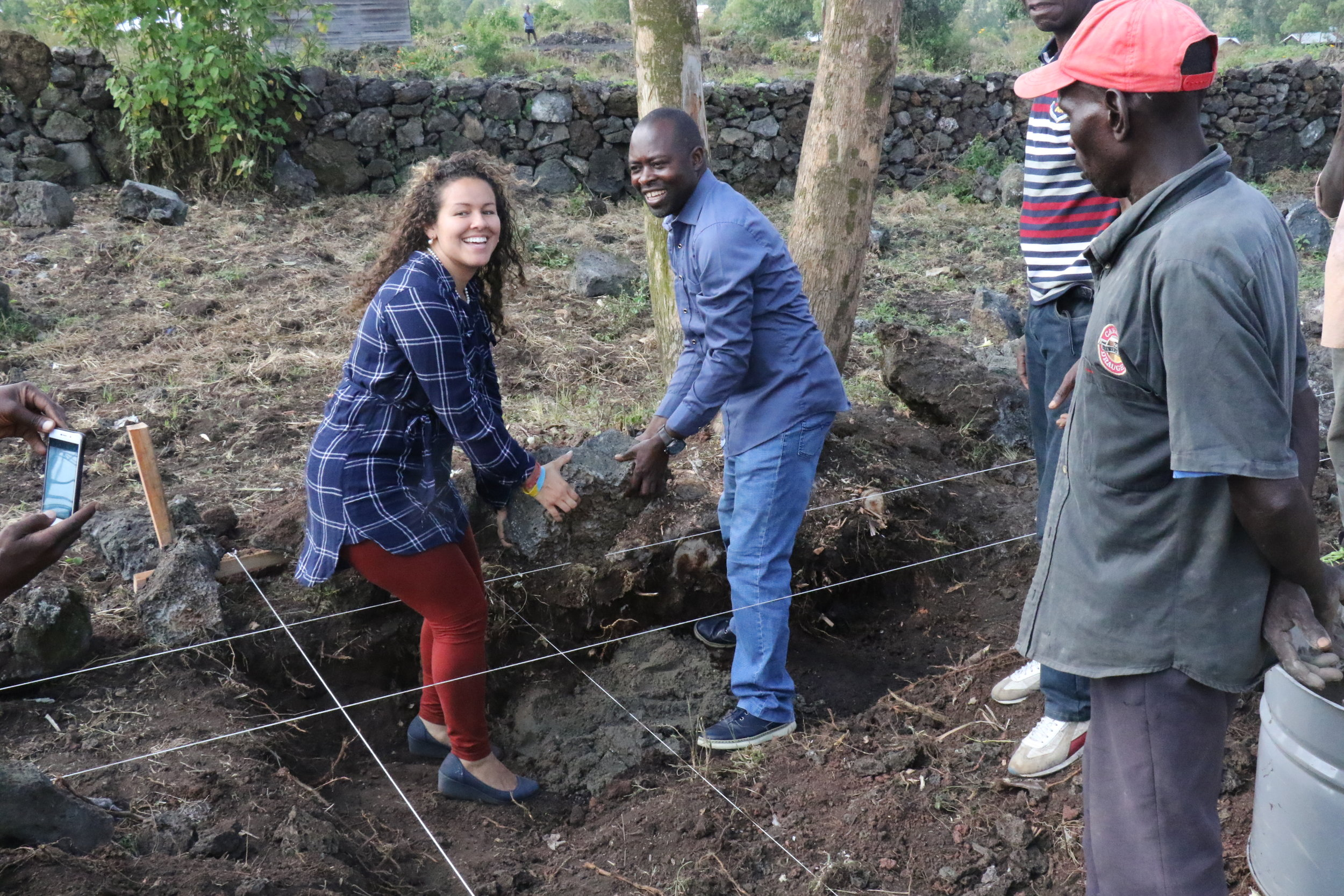 Amethyst Roth and Euclide Mugisho, two of the founders of the community lay the corner stone to start the building process.