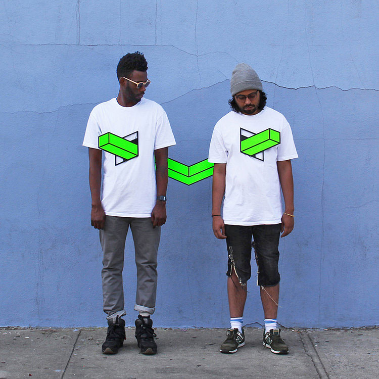 A photo where two men are standing, wearing white t-shirts, and there is an optical illusion that makes it look like a neon green L-shaped thing is going through both of their chests. (It looks cool, not gruesome.)