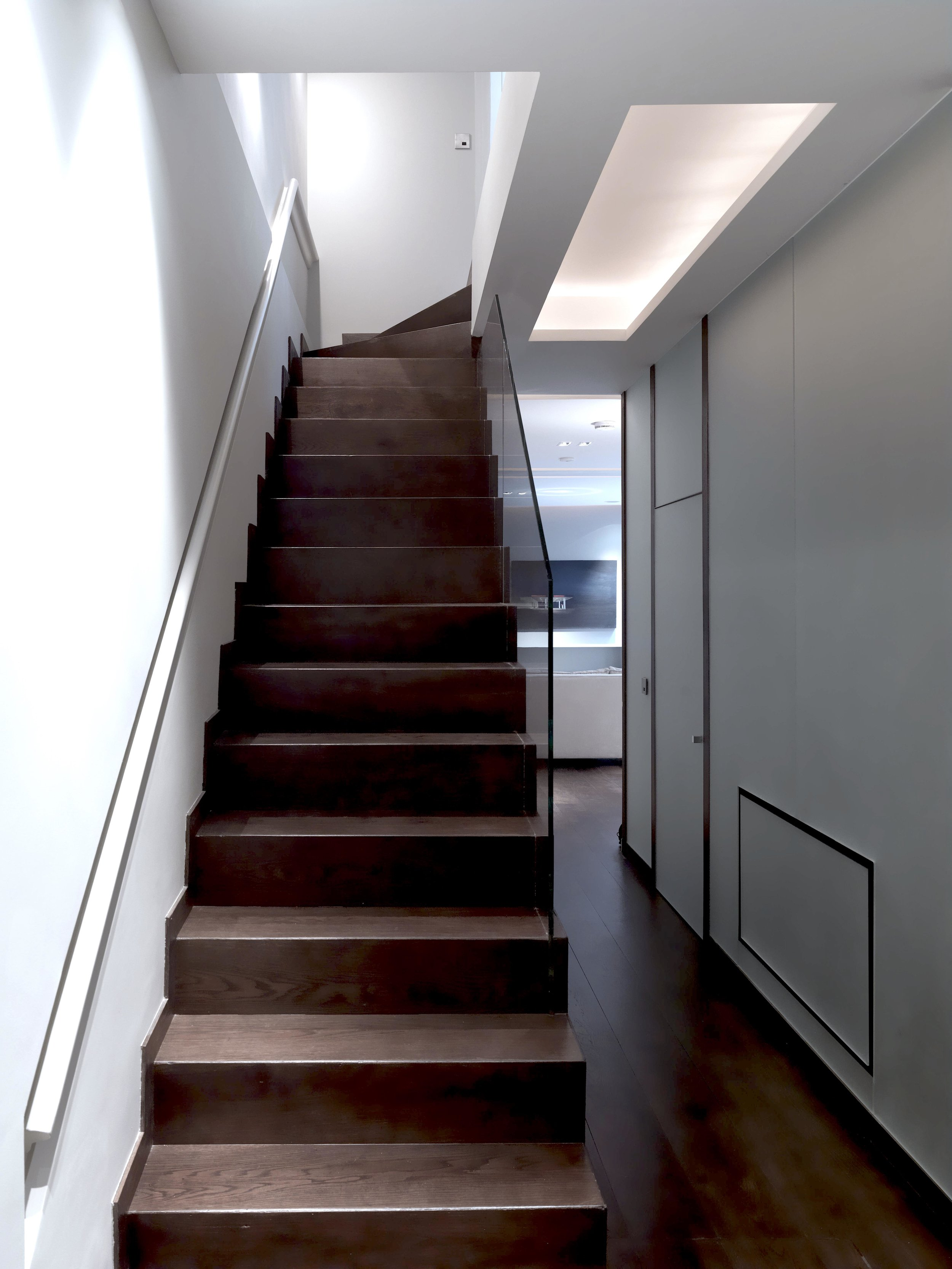 Stairs to Lower Ground Floor in more contemporary style, with sandblasted mirror wall to reflect light, with ceiling light details