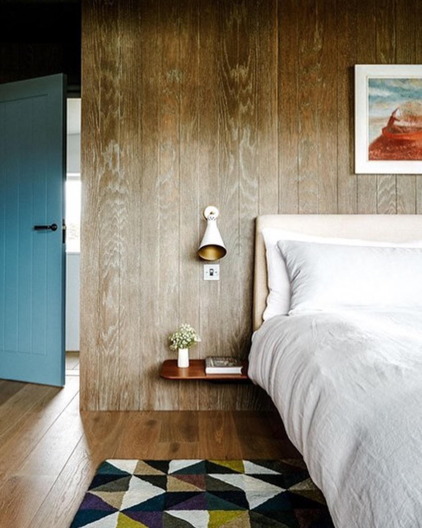 Master bedroom, oak wall panelling and flooring, painted doors, dark bronze hardware, mid-century wall lights, geometric rug
